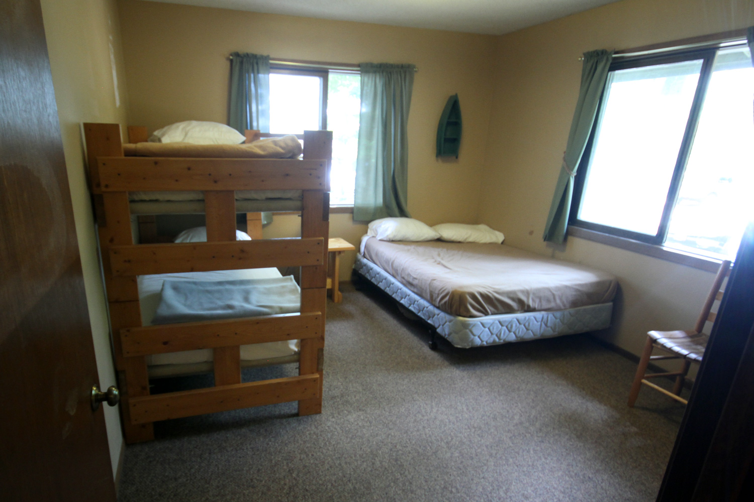 Large bedroom with double bed, 2 bunks, and 1/2 bath